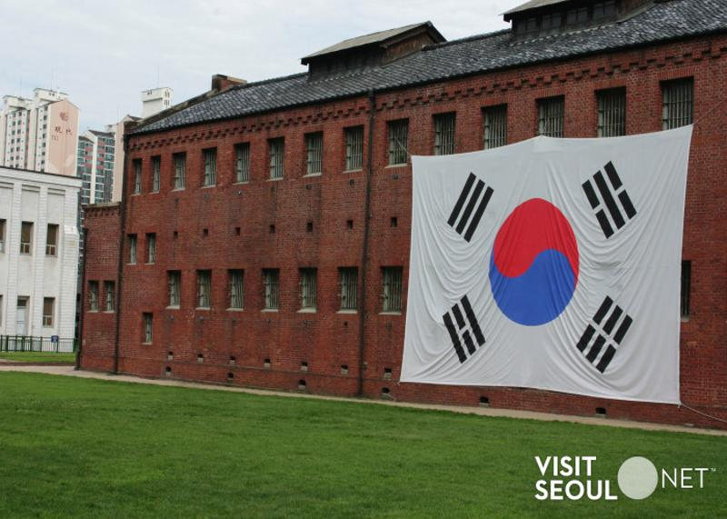 This is a picture of the exterior of Seodaemun Prison History Hall. This building is a two-story building made of red bricks. There is a large Taegeukgi hanging on the right side of the building.