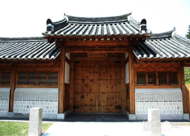 This is a picture of the entrance to the Korean Furniture Museum. This is the gate of a hanok with tile roofs. There is a signboard with the writing 'Korea Furniture Museum'.
