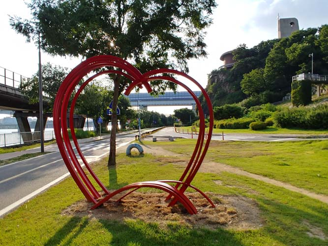 A red metal structure coming up from the ground forming into the shape of a heart