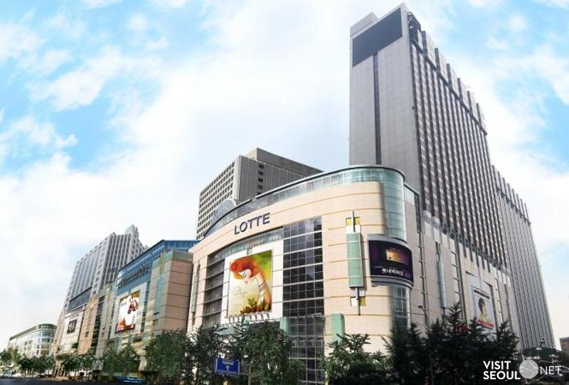 This is the exterior of the main building of the Lotte Department Store. There is a logo, 'LOTTE' on the outer wall of a large building. There is a picture hanging on the wall.