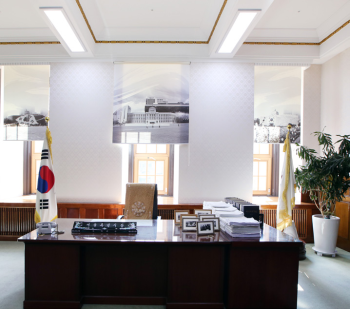 Old Mayor's Office exhibit showing the desk, Korean flag, and three windows in the background with the sun shining in