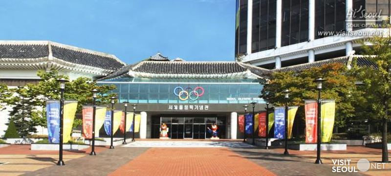This is a picture of the exterior of the Seoul Olympic Memorial Hall. At the entrance, the word 'Seoul Olympic Memorial Hall' is written along with Olympic flag.