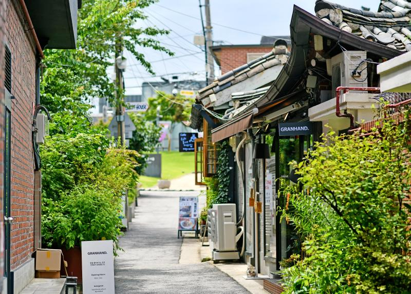 This is a picture of Samcheong-dong Alley. There are hanok-style buildings and green trees on both sides of the alley. There is a sign in front of the buildings, and it looks like a cafe or restaurant.