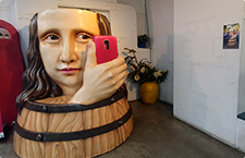 A sculpture of a girl taking a smartphone picture with the phone held close to her face as she pops only her head outside of the barrel she is in